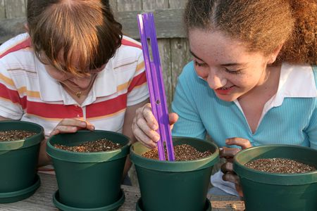Two young girls working together on a science project, planting seeds.