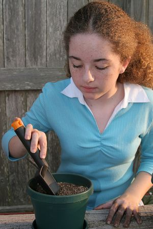 A student digging a hole in the dirt preparing to plant seeds for a science project. Stock Photo - 255140
