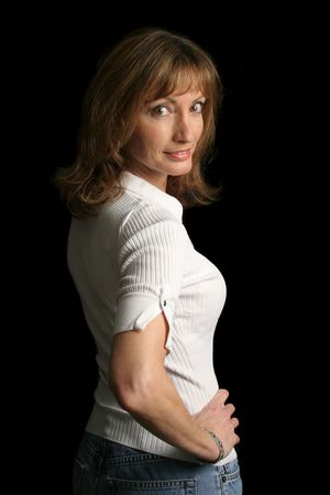 A beautiful, mature woman against a black background.  She has a flirty expression. photo