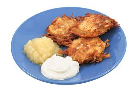 menora: Potato pancakes (latkes) for Hanukah, served with sour cream and applesauce. Isolated.
