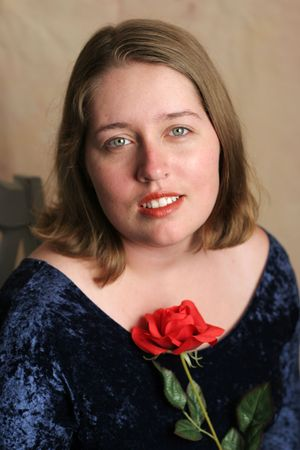 A beautiful high school senior posing for her senior portrait, with a red rose. photo