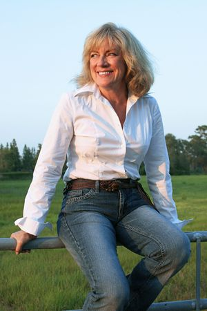 fifty: A beautiful, mature woman sitting on a fence on her ranch.