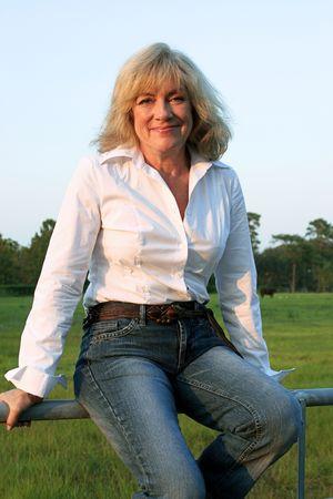 donne mature sexy: Una bella, paese occidentale donna seduta su una recinzione a suo ranch.