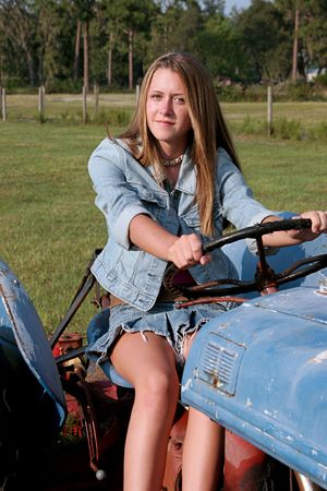 A beautiful blond country girl driving a tractor.