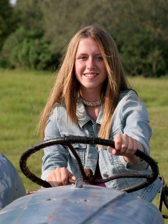 falda corta: Hija de un granjero hermoso detr�s de la rueda de un tractor antiguo.
