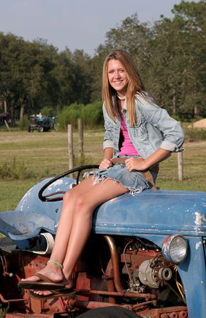 long skirt: A vertical view of a farmers daughter sitting on a tractor.