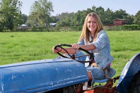 A beautiful farmers daughter driving a tractor through a green field. photo