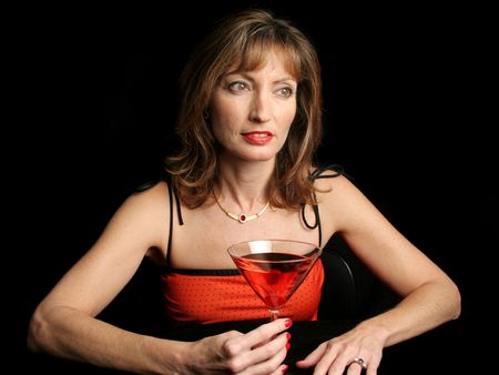 A beautiful woman alone in a bar, drowning her sorrows in a cosmopolitan.  Black background. photo