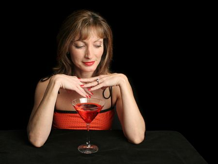 A beautiful woman in red, drinking a cosmopolitan with a suggestive expression.  Photographed against a black background. photo