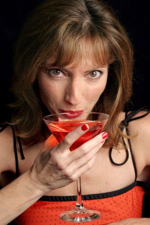 A beautiful woman in red sipping a cosmopolitan. photo