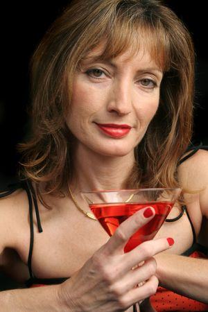 A beautiful woman a bit tipsy enjoying her last drink of the night. (focus is on her eyes) Stock Photo