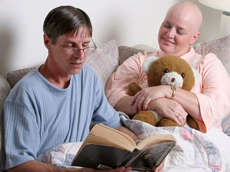 A man reading the bible to a cancer patient. (focus is on the reader)
