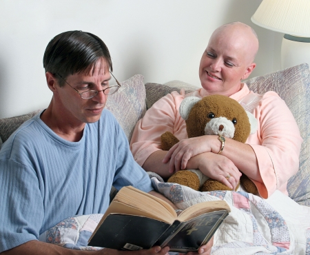 survive: A man volunteering to read the bible to a cancer patient. (focus is on the womans face) Stock Photo