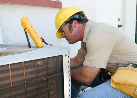 repairman: An air conditioning repairman working on a compressor unit. Stock Photo