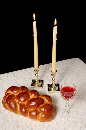 sabbath: A table set for Shabbat with lighted candles, challah bread and wine. Vertical view with black background.