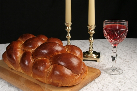 A table set for Shabbat with challah bread, candlesticks and wine.  Black background, complete view. Stock Photo