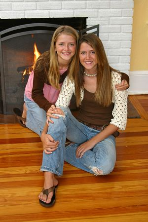 beside: Beautiful blond sisters sitting beside the fireplace.
