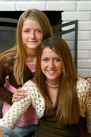 A closeup portrait of two beautiful sisters in front of a fireplace. Stock Photo - 1406789