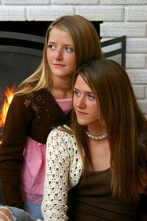 Two beautiful teenaged sisters sitting beside the fireplace Stock Photo - 1406788