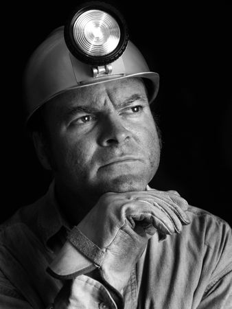A black and white portrait of a coal miner with a thoughtful expression. photo