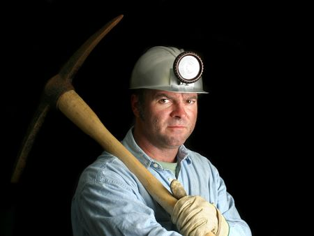 A coal miner with his pickax, in the darkness of a mine shaft. photo