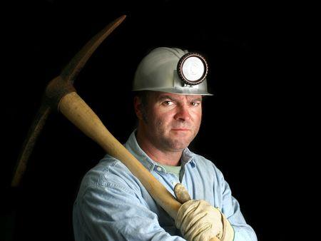 Un minero del carbón con su pico, en la oscuridad de una mina eje.  Foto de archivo