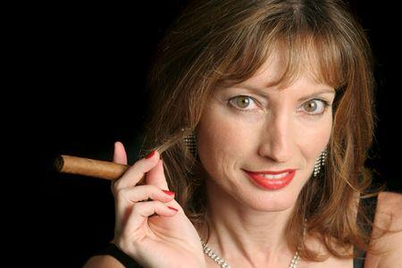 donna ricca: Una bella, sofisticata donna con un sigaro, contro uno sfondo nero.  Archivio Fotografico