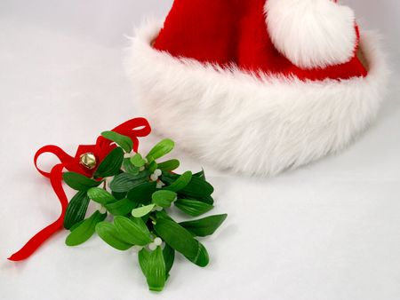 A red santa claus hat with a sprig of mistletoe. photo