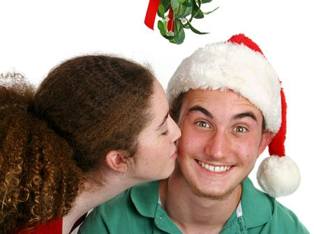 A teen girl kissing a very surprised boy under the mistletoe. photo
