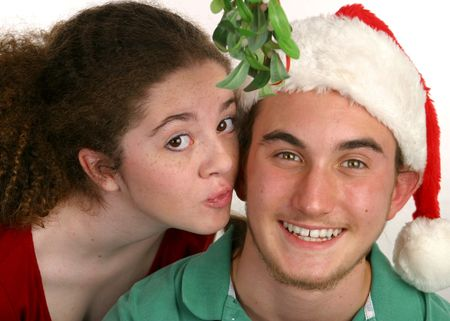 A teenaged girl kissing a teenaged boy under the Christmas mistletoe. Stock Photo - 277476