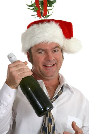 A drunk man under the mistletoe holding a bottle of champagne. Imagens