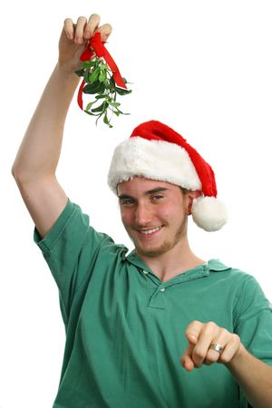 pointing herbs: A teen boy in a santa hat holding mistletoe and pointing toward the camera. Isolated. Stock Photo