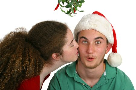 A teen girl kissing a surprised looking teen boy under the mistletoe.  Isolated