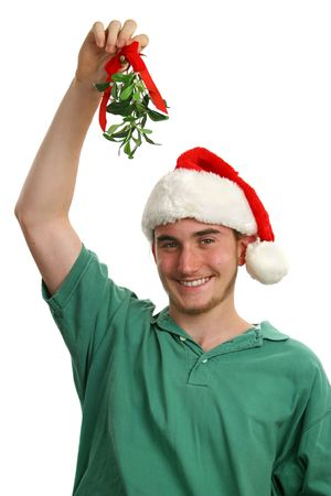 A teen boy wearing a santa hat and holding mistletoe over his head. Isolated. Stock Photo - 281024
