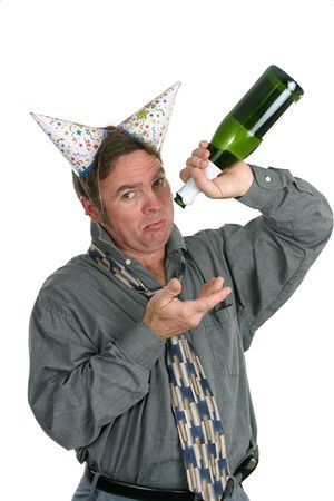 A man in a party hat holding an empty champagne bottle and looking sad. photo