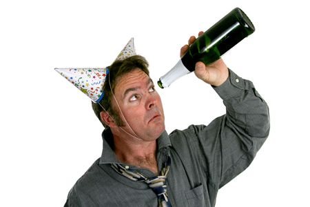 sadly: A man wearing two party hats and looking sadly up inside and empty bottle of champagne. Stock Photo