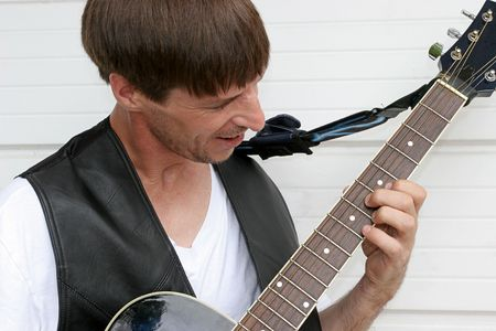 A closeup of a blues musician playing his guitar.