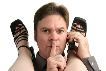 affairs: A man having an office affair answering his cell phone and quieting his partner.