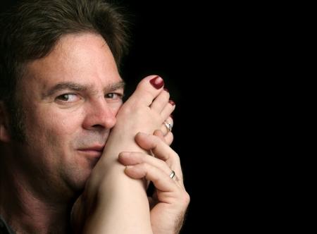 Een knappe man kuste een vrouw voet. Zwarte achtergrond en ruimte voor tekst. Stockfoto