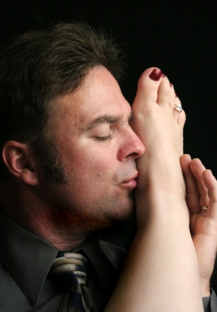 A handsome man kissing a womans foot. Stock Photo