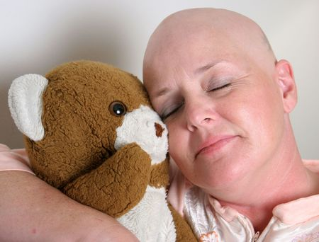 A medical patient cuddling with a teddy bear for comfort. Stock Photo