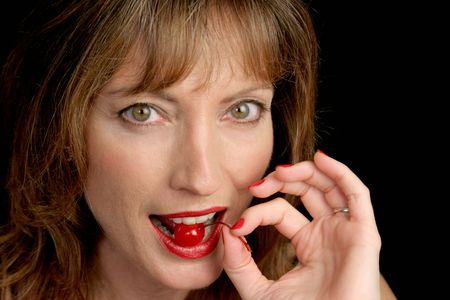 A closeup of a beautiful woman's face as she bites into a juicy red cherry. Stock Photo - 293137