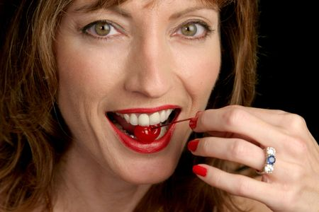provocative food: A beautiful woman biting into a maraschino cherry.