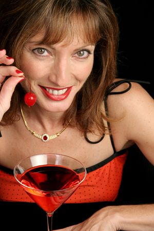 provocative food: A beautiful woman in red holding a dripping cherry and smiling. Stock Photo