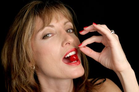 sensuous: A beautiful, sensuous woman biting into a cherry. Stock Photo