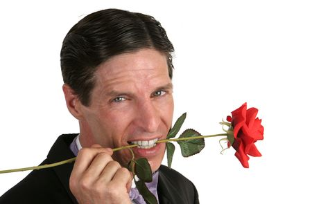 A handsome man holding a rose between his teeth. photo
