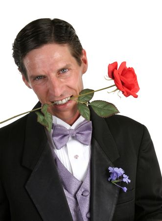 A handsome man in a tuxedo with a red rose between his teeth photo