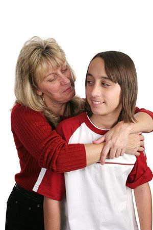 A mother trying to give her skeptical son a hug. Isolated.