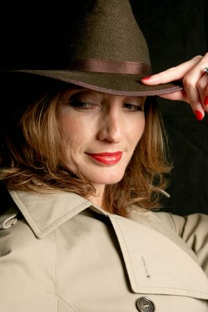 secretive: A beautiful woman in a trenchcoat and fedora hat, looking behind her in a secretive way.