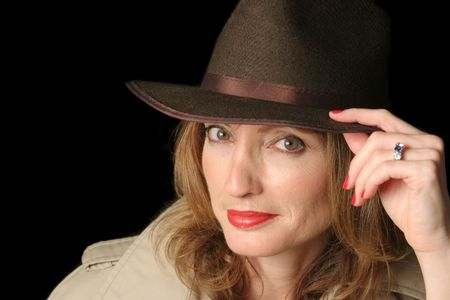 marital: A beautiful woman in a smiling in a hat and trenchcoat over a black background.  Possible marital role playing.
